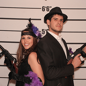 Des Moines Murder Mystery party guests pose for mugshots